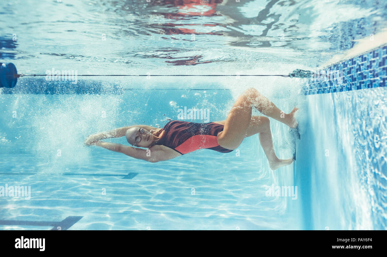 Shot of professional swimmer turning over underwater while swimming. Female swimmer in action inside pool. Stock Photo