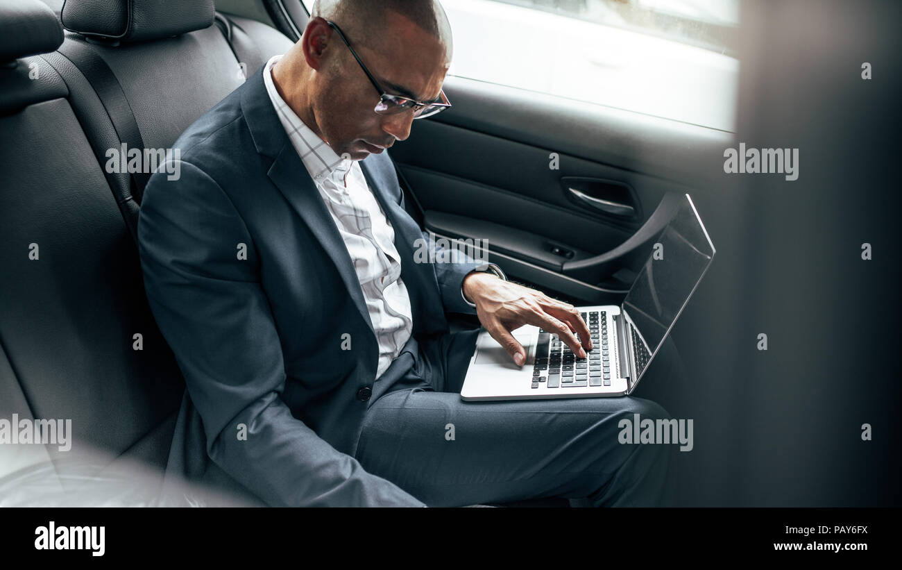 Businessman working on laptop computer while commuting to office in his sedan in back seat. Entrepreneur managing business work on the move sitting in - Stock Image