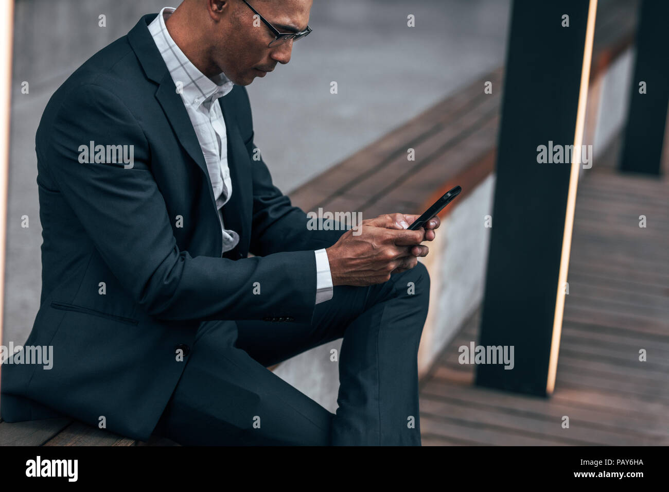 Entrepreneur typing text in mobile phone sitting on side railing outdoors. Businessman sitting outdoors managing work using cell phone. - Stock Image