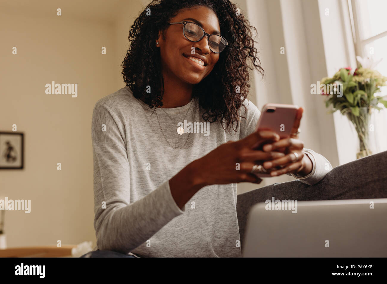 Smiling businesswoman sitting on sofa at home using mobile phone while working on laptop. Woman working on laptop computer at home and managing her bu - Stock Image
