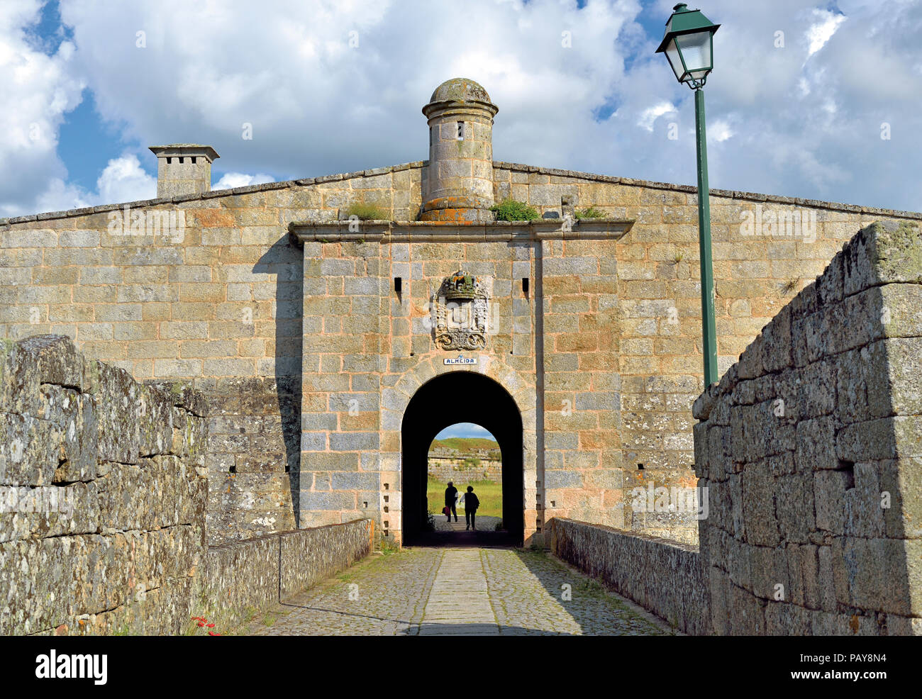 Two people walking through a tunnel of a historic town gate - Stock Image