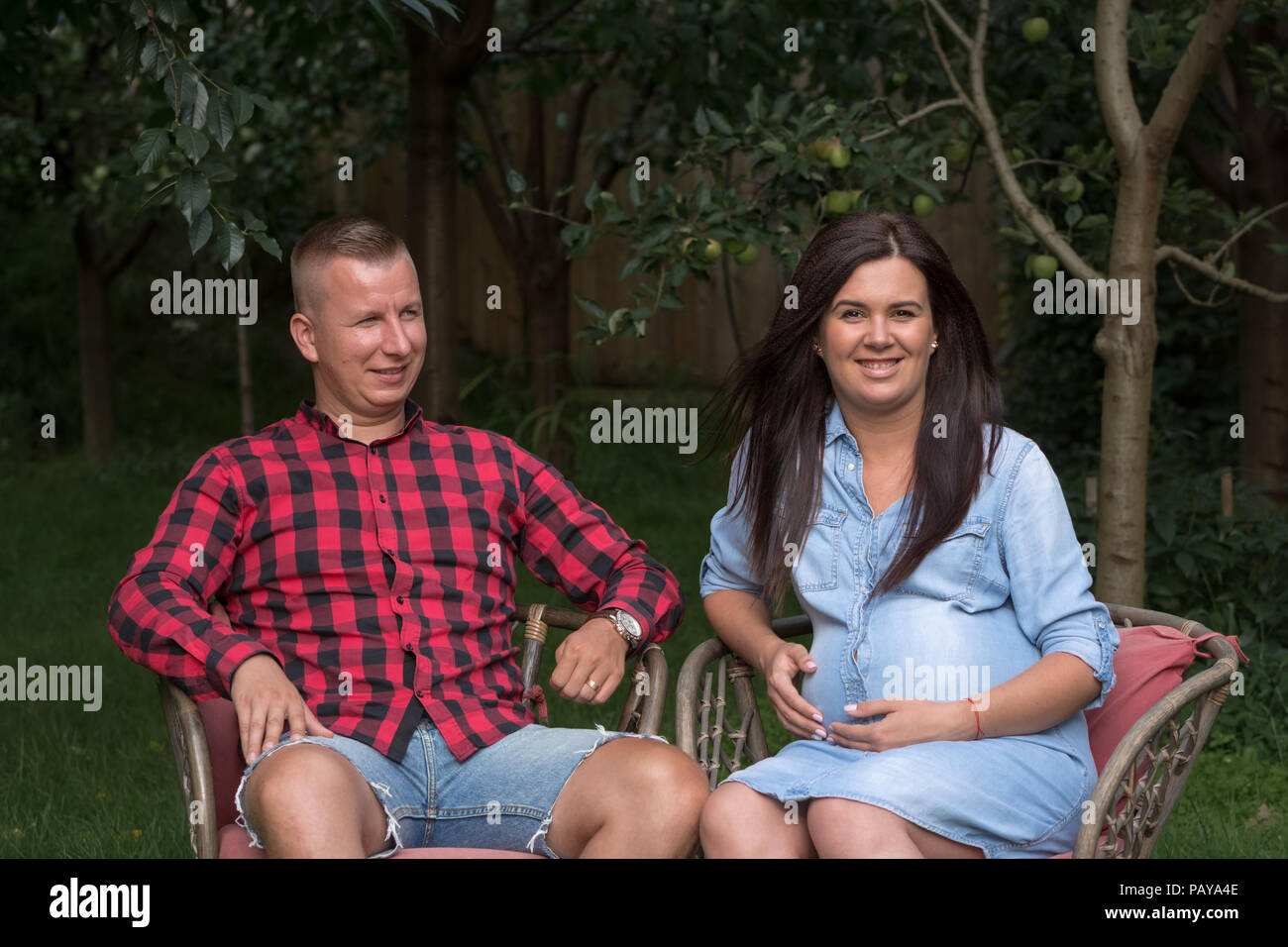 Adult male and a pregnant woman relax in the summer in the garden - Stock Image