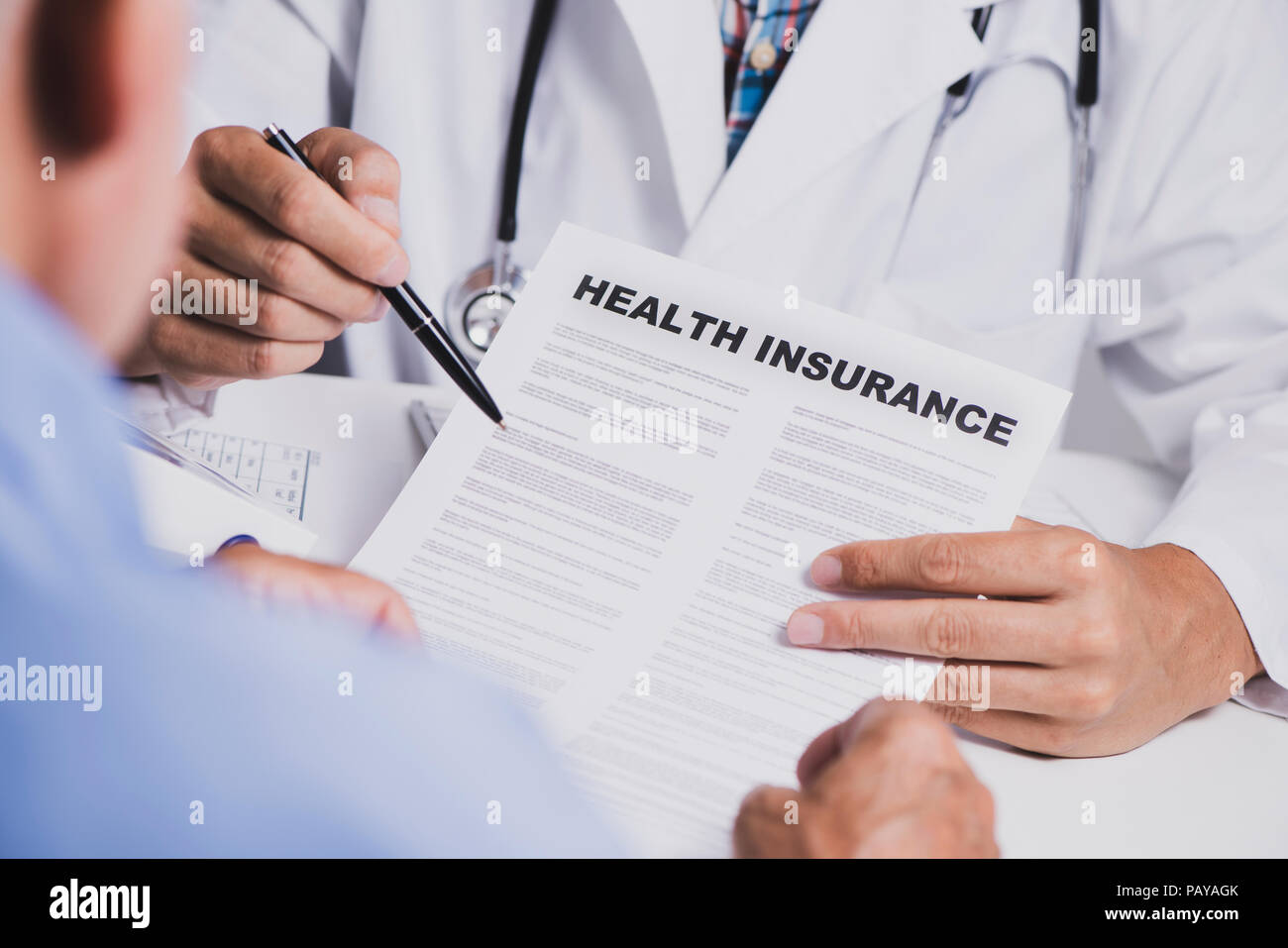 closeup of a caucasian doctor man, in a white coat, showing the clauses of a health insurance policy to a senior caucasian man, sitting both at his de - Stock Image