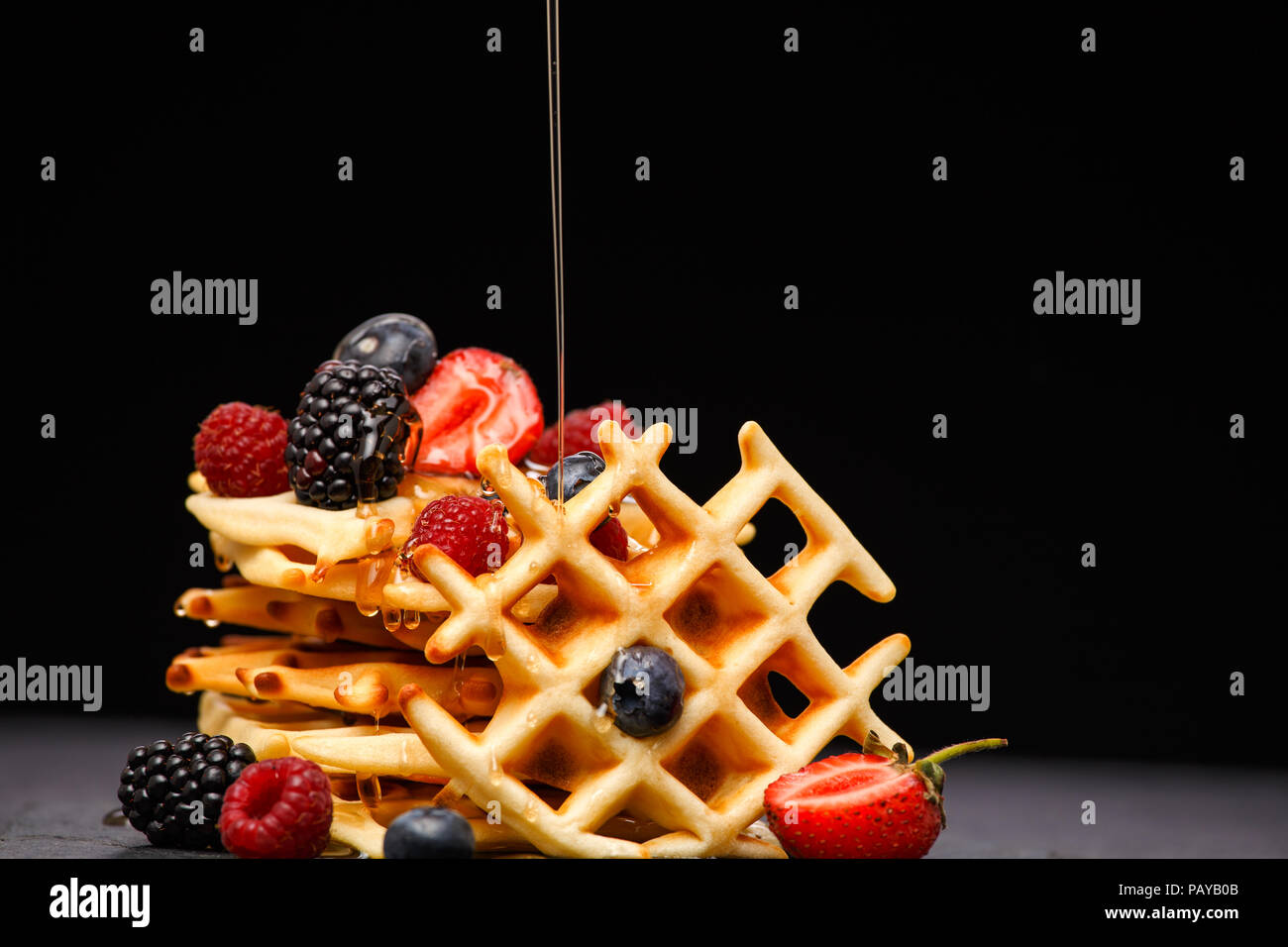 Photo of viennese wafers with berries pouring honey on black empty background - Stock Image