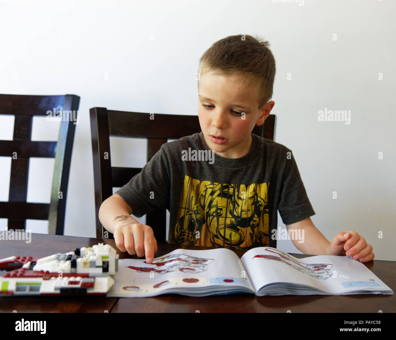 A young boy (6 yr old) concentrating on making his Lego Star Wars fighter Stock Photo
