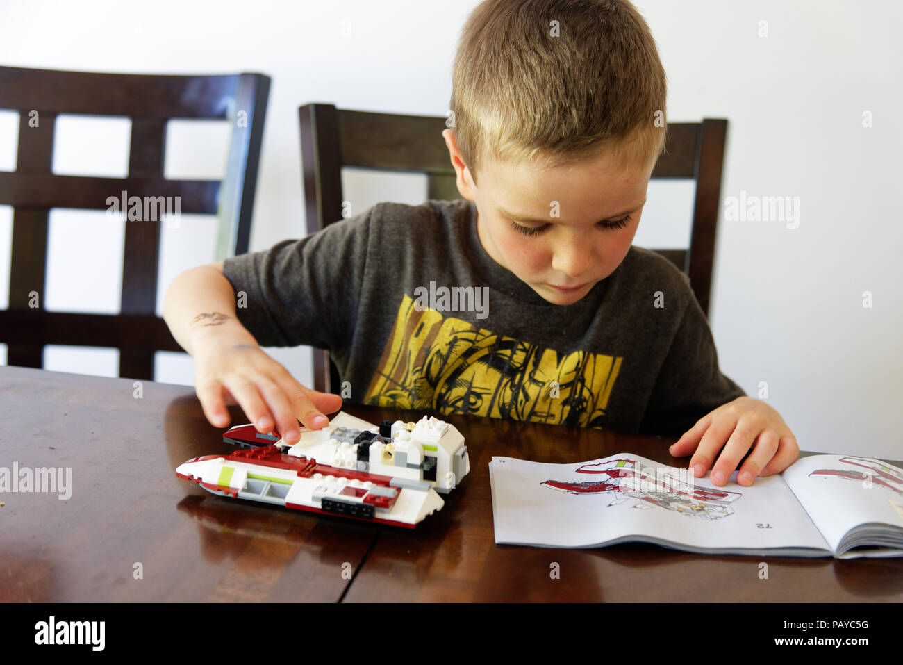 A young boy (6 yr old) concentrating on making his Lego Star Wars fighter - Stock Image