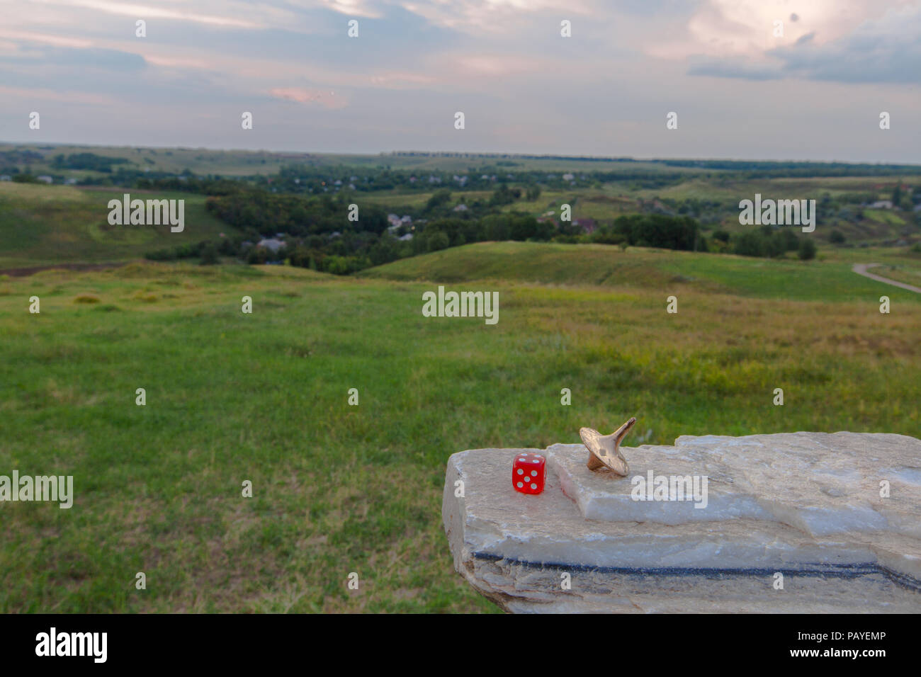 gyroscope gold lies on a granite on a grass hill background - Stock Image