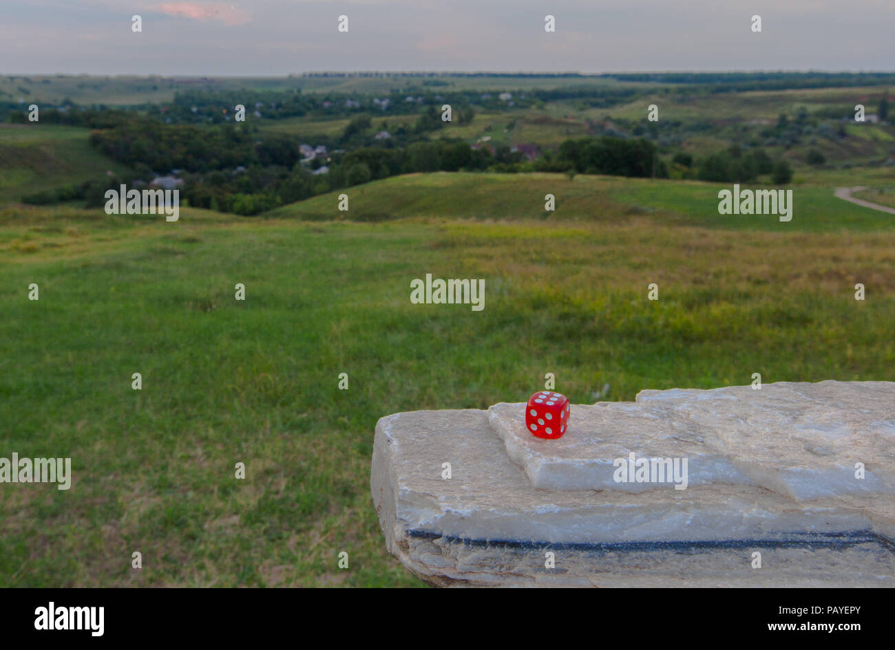 red dice lies on a granite on a grass hill background - Stock Image