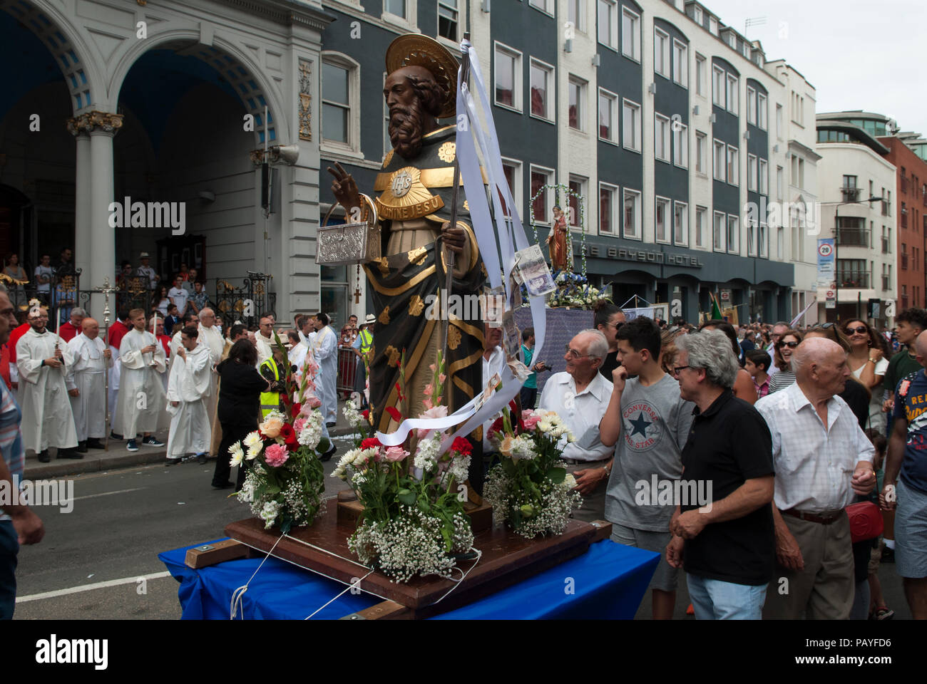 Saint Peters,  St Peters Italian Church London outside priests watching floats go past  HOMER SYKES - Stock Image