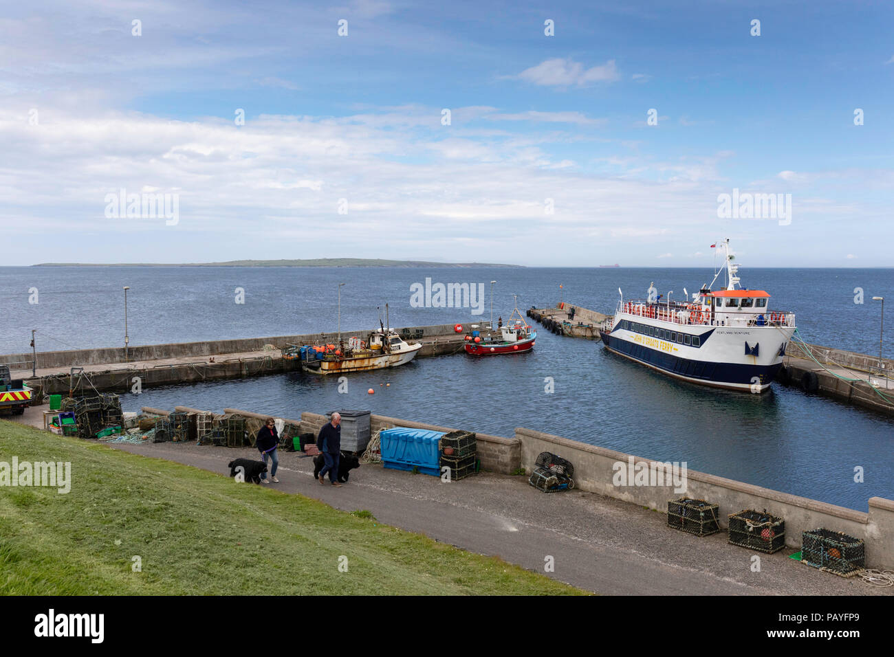 Ferry and harbour with Orkeney in the background at John O'Groats - Stock Image