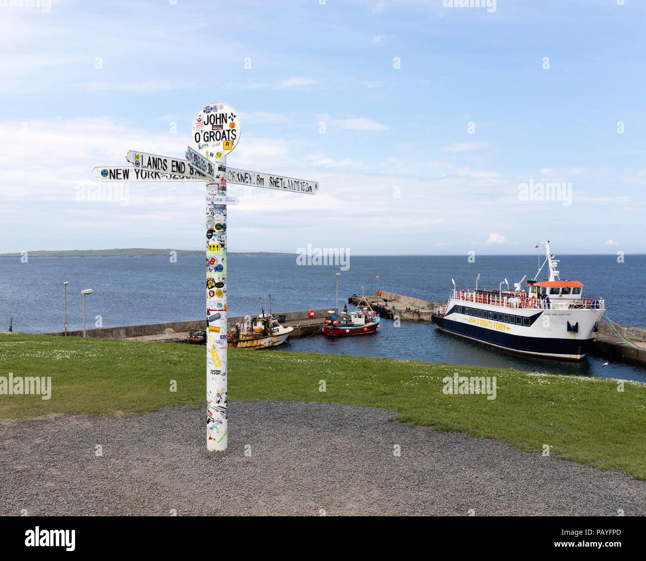 The Sign Post indicating the end of the road at John O'Groats with the harbour, Ferry and Orkeney in the background - Stock Image