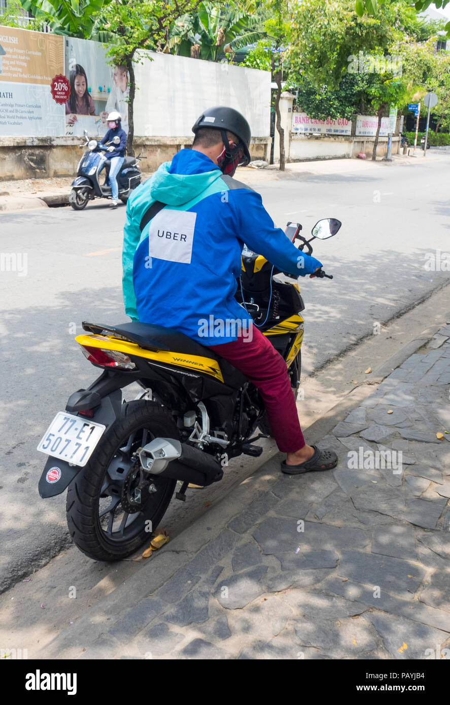 Ride sharing Uber motorcyclist on his motorbike in Ho Chi