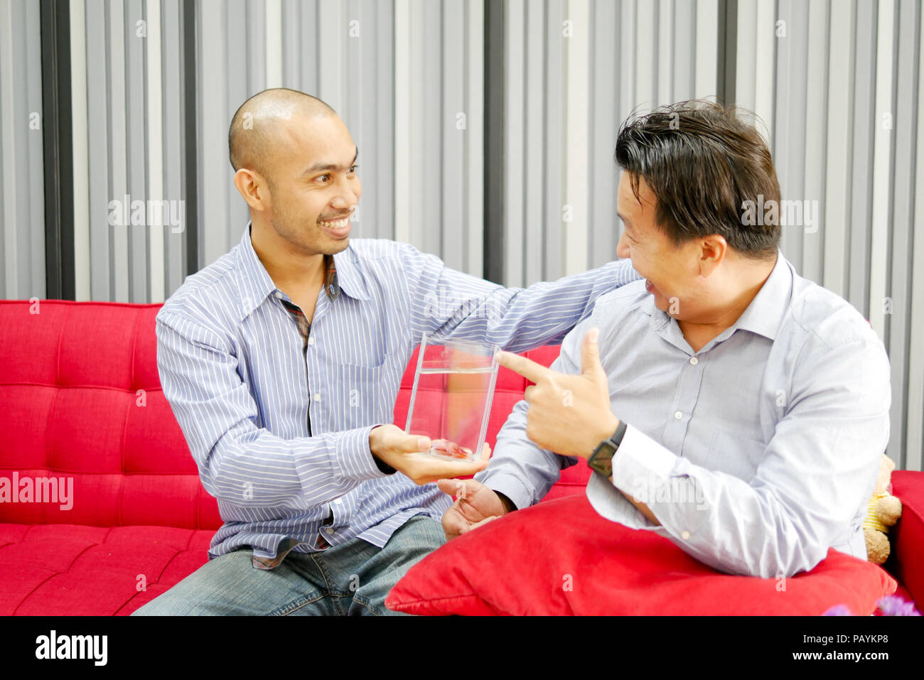 Two asian guys are seeing betta fish in the glass and very happy Stock Photo