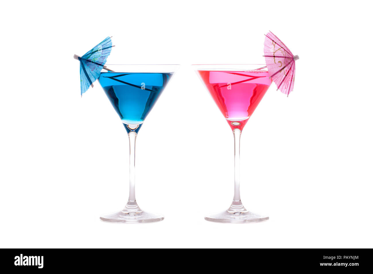 His and hers party or vacation cocktails. Neon blue and pink summer fun alcoholic drinks in cocktail glasses with decorative umbrellas. Isolated again - Stock Image