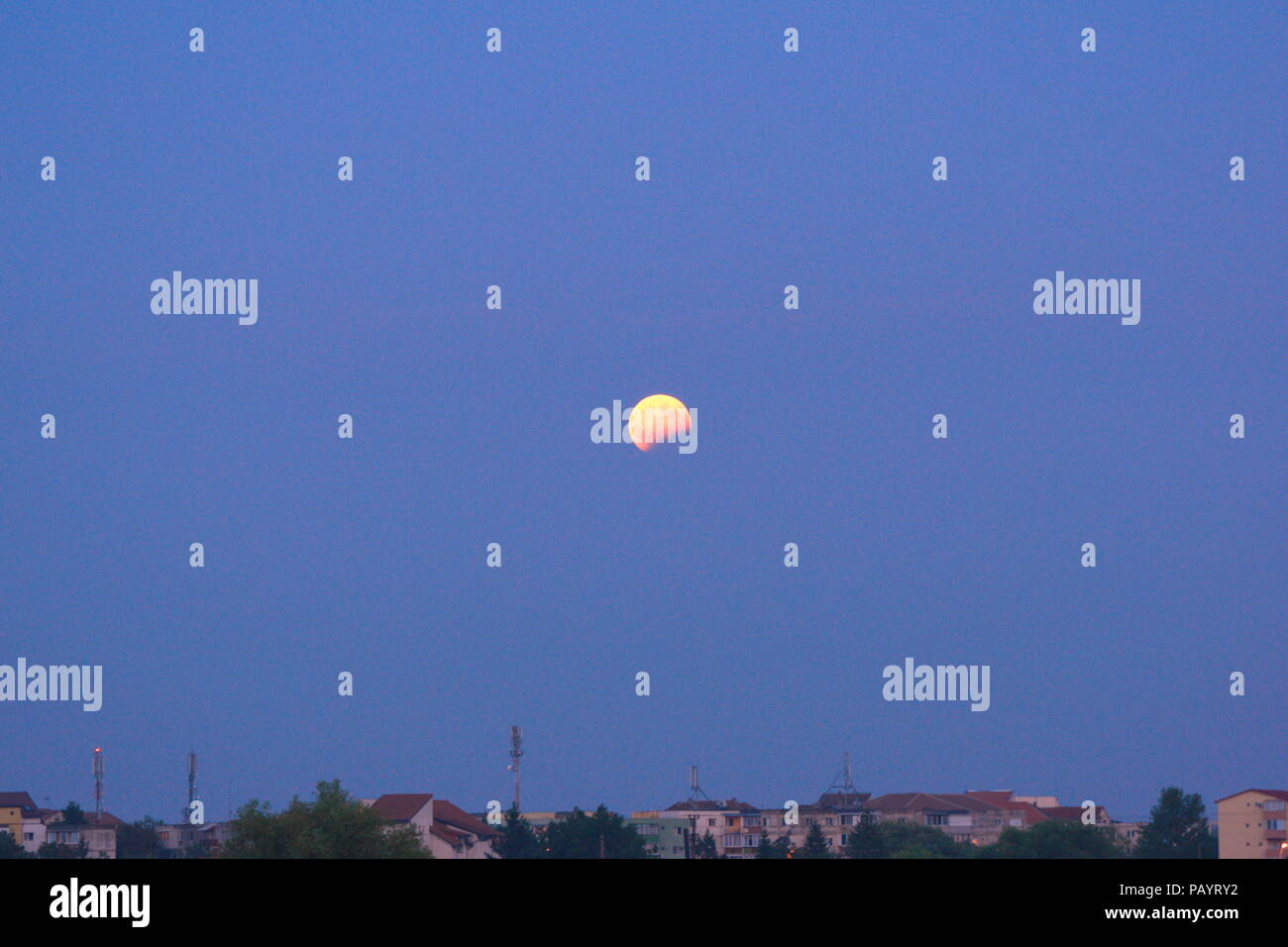 Moon eclipse over the town - Stock Image