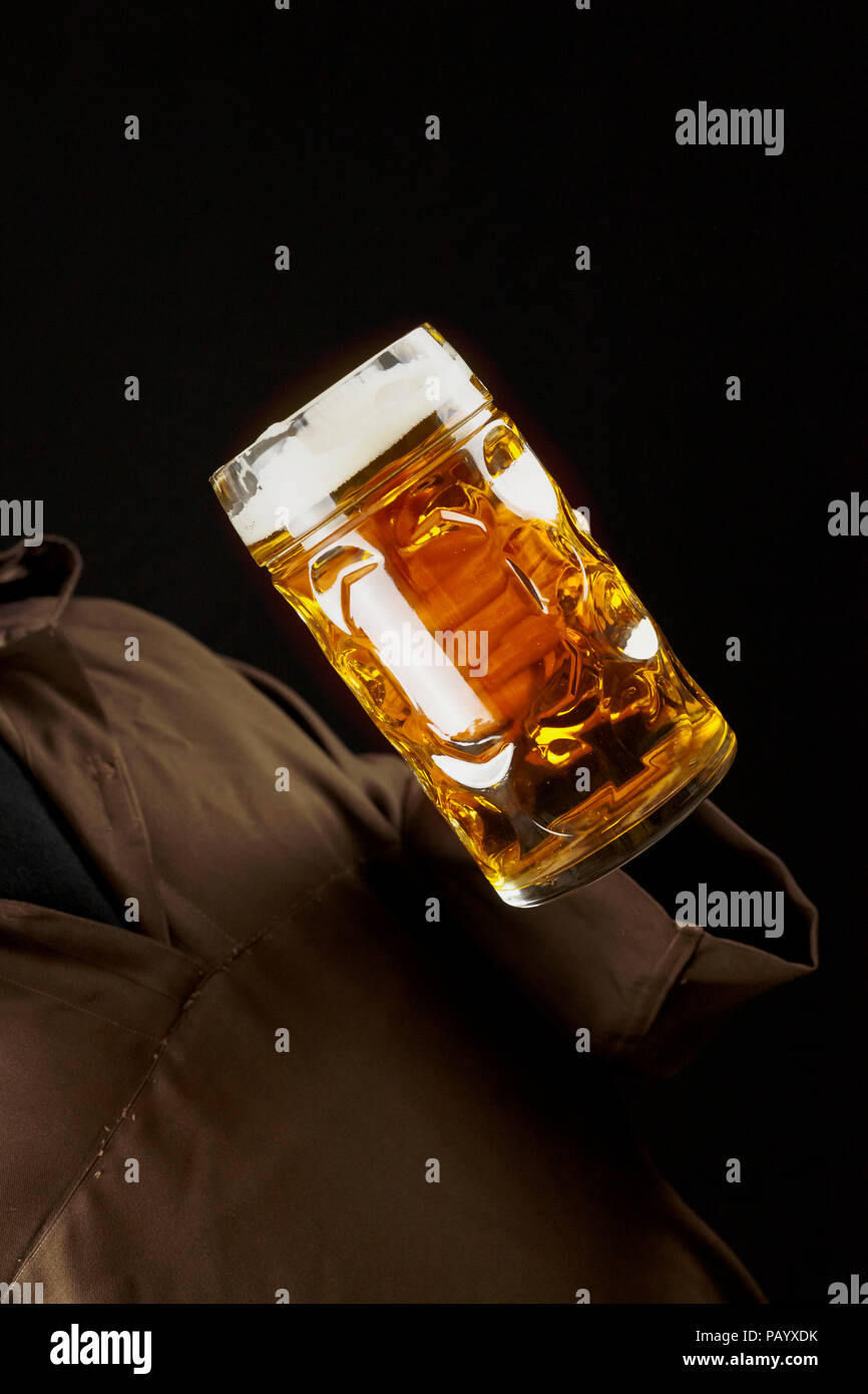 Delicious beer in a giant glass mug, held by a friar, dutch angle shot. - Stock Image