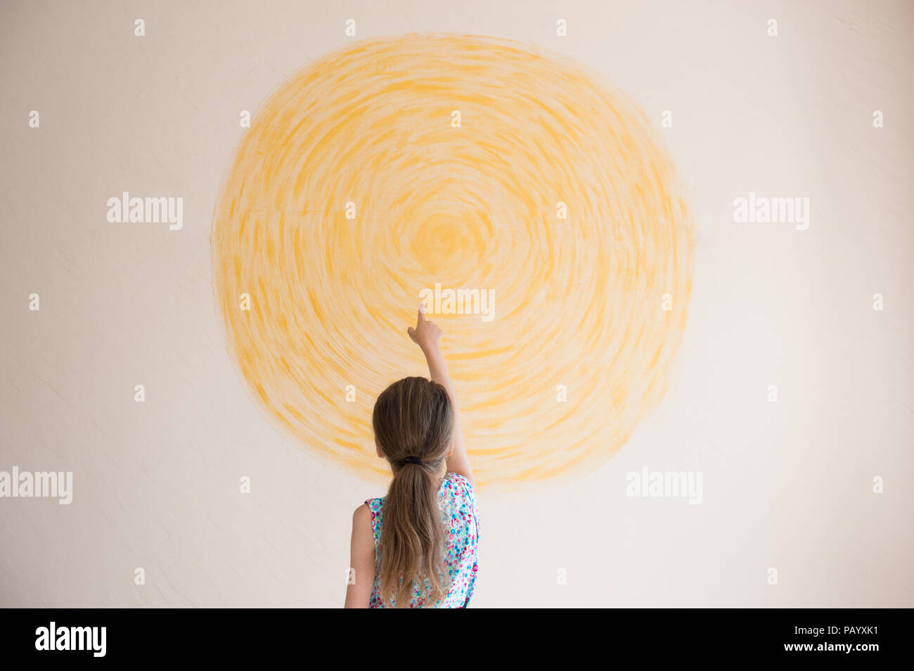 little girl pointing finger at yellow sun painted on wall indoors - Stock Image