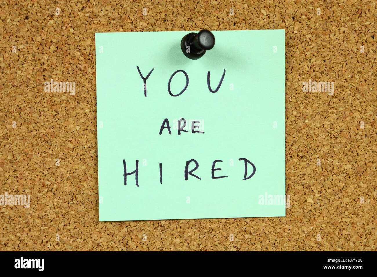 Green small sticky note on an office cork bulletin board. You are hired message. Career success, new employment. - Stock Image