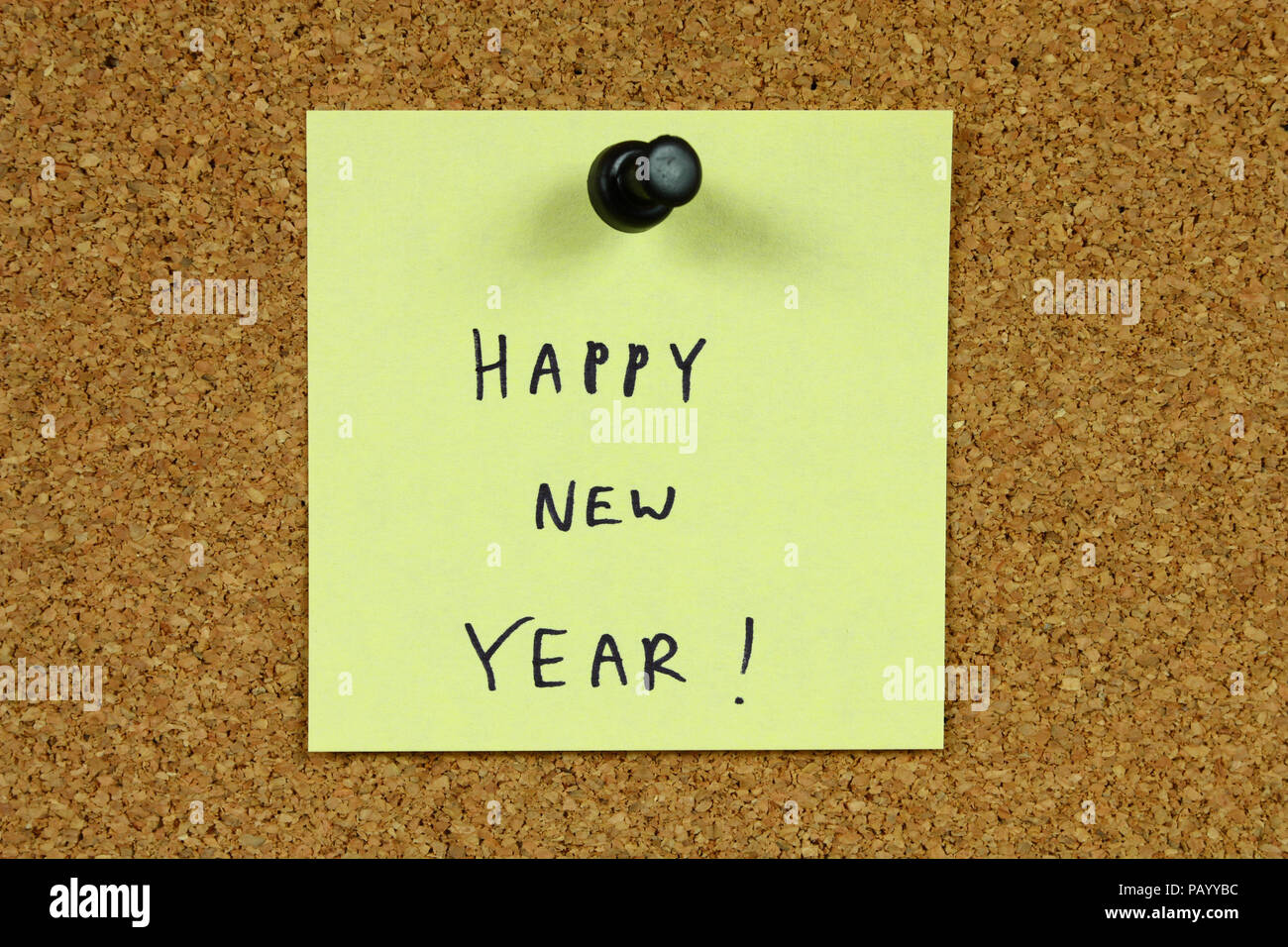 Yellow small sticky note on an office cork bulletin board. Happy New Year! - Stock Image