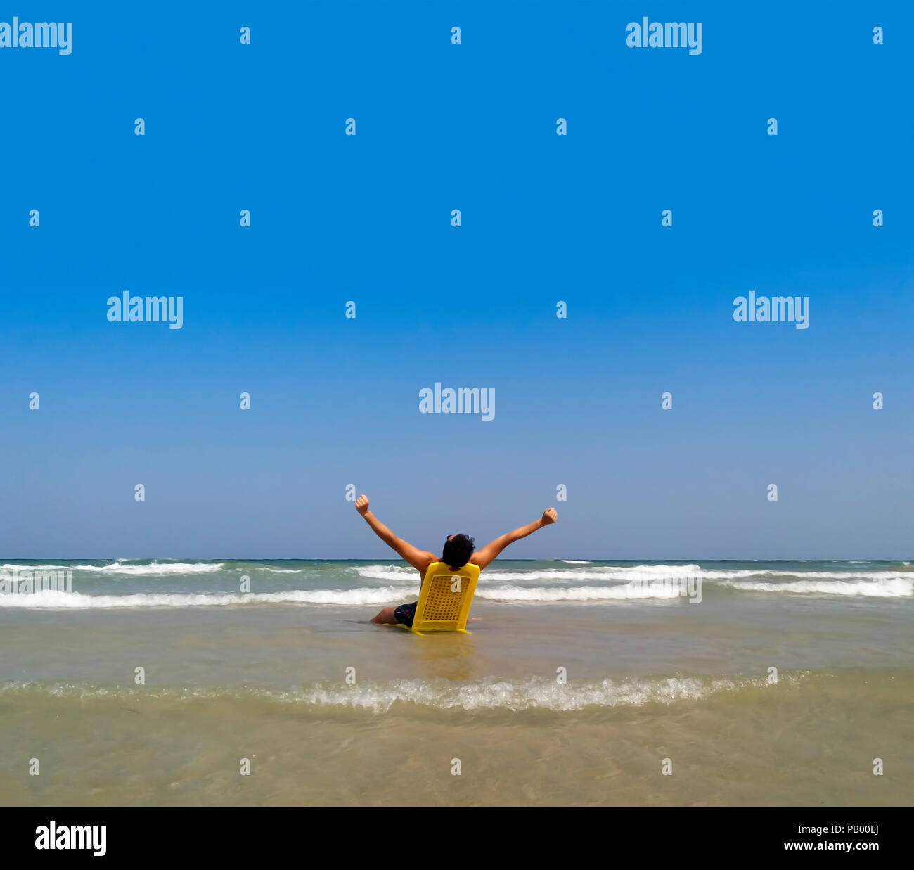 a man relaxes sitting on the sea beach; satisfaction; - Stock Image
