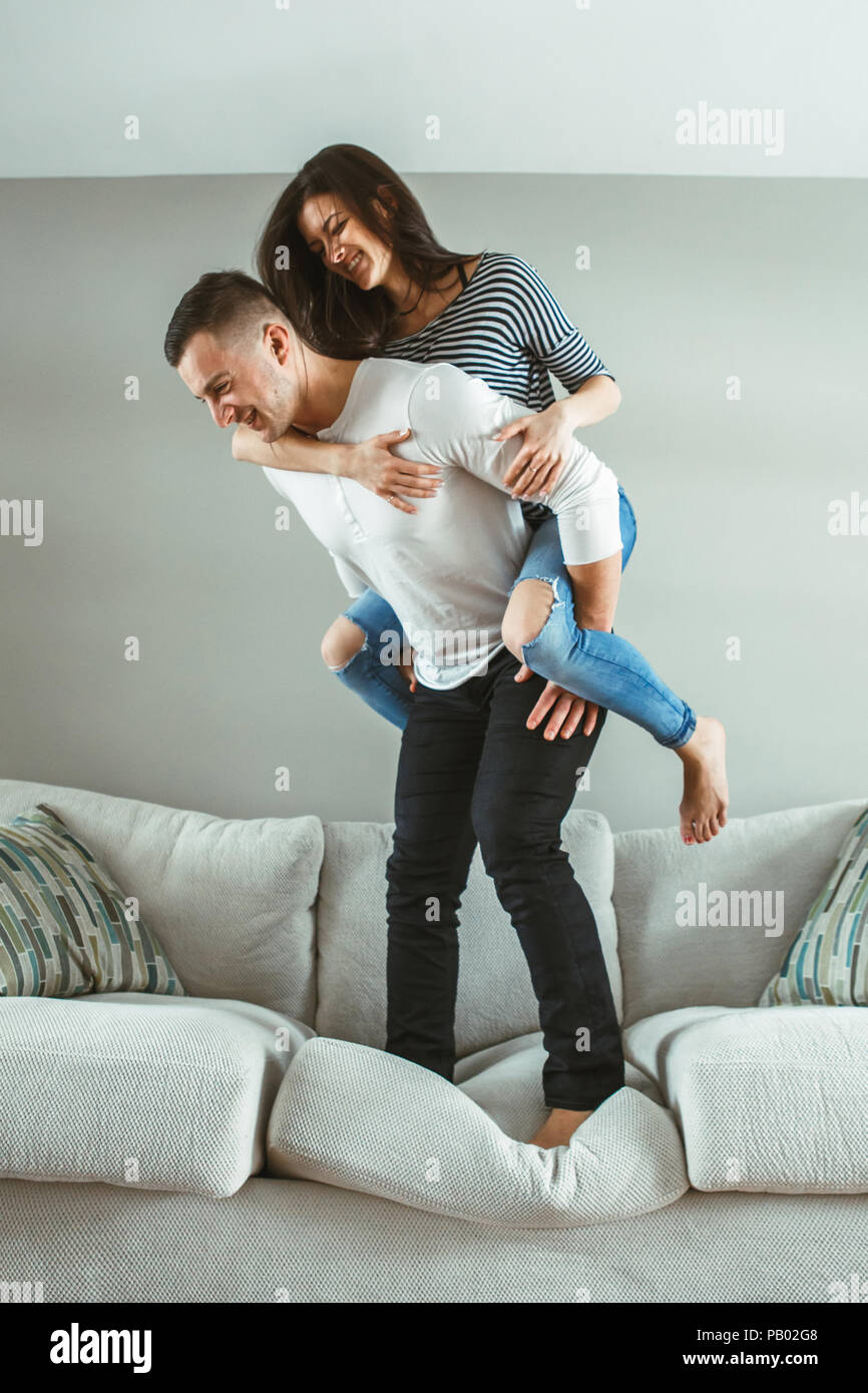 Portrait of young beautiful funny couple man woman in love having fun standing on bed piggyback indoors at home, toned with filters - Stock Image