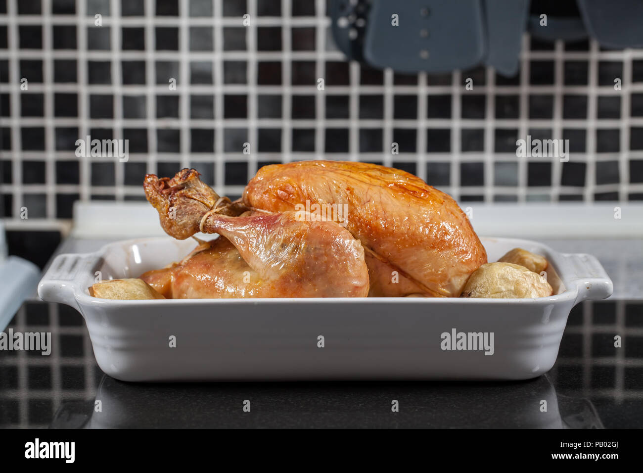 Whole hot oven cooked roast chicken. Prepared sunday meal with potatoes on the kitchen worktop ready for carving and serving for dinner. - Stock Image