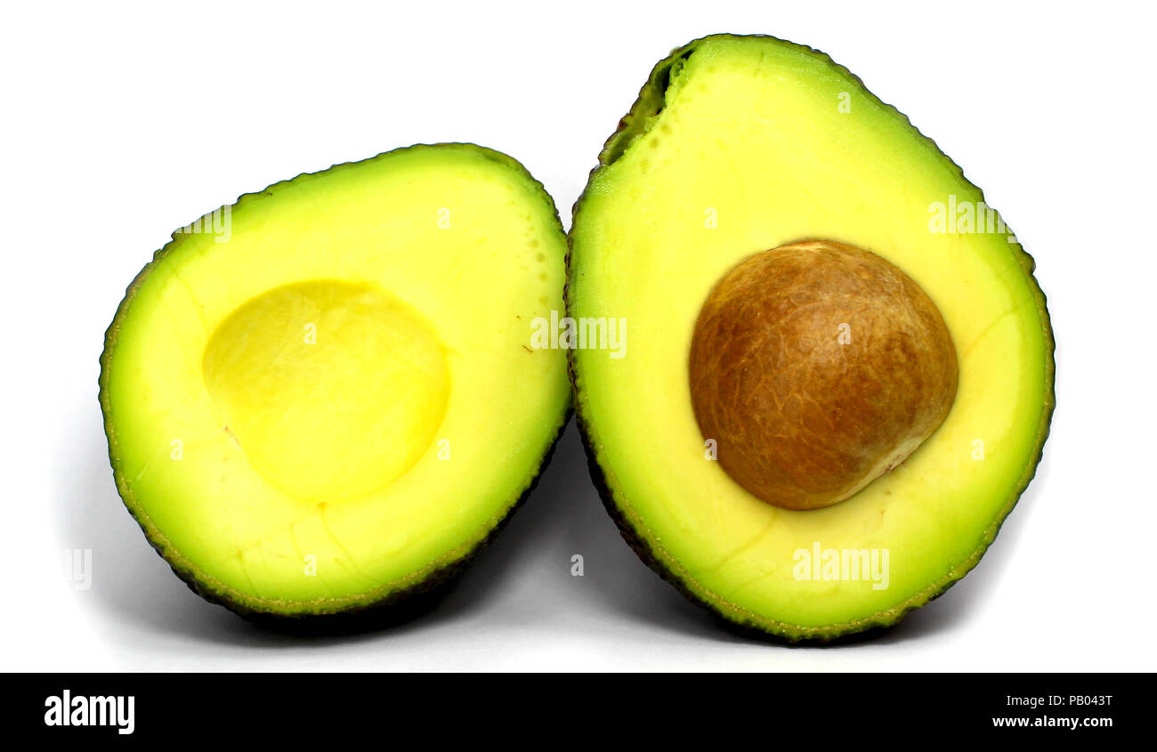halved fresh avocado sliced and isolated on white background with core - Stock Image