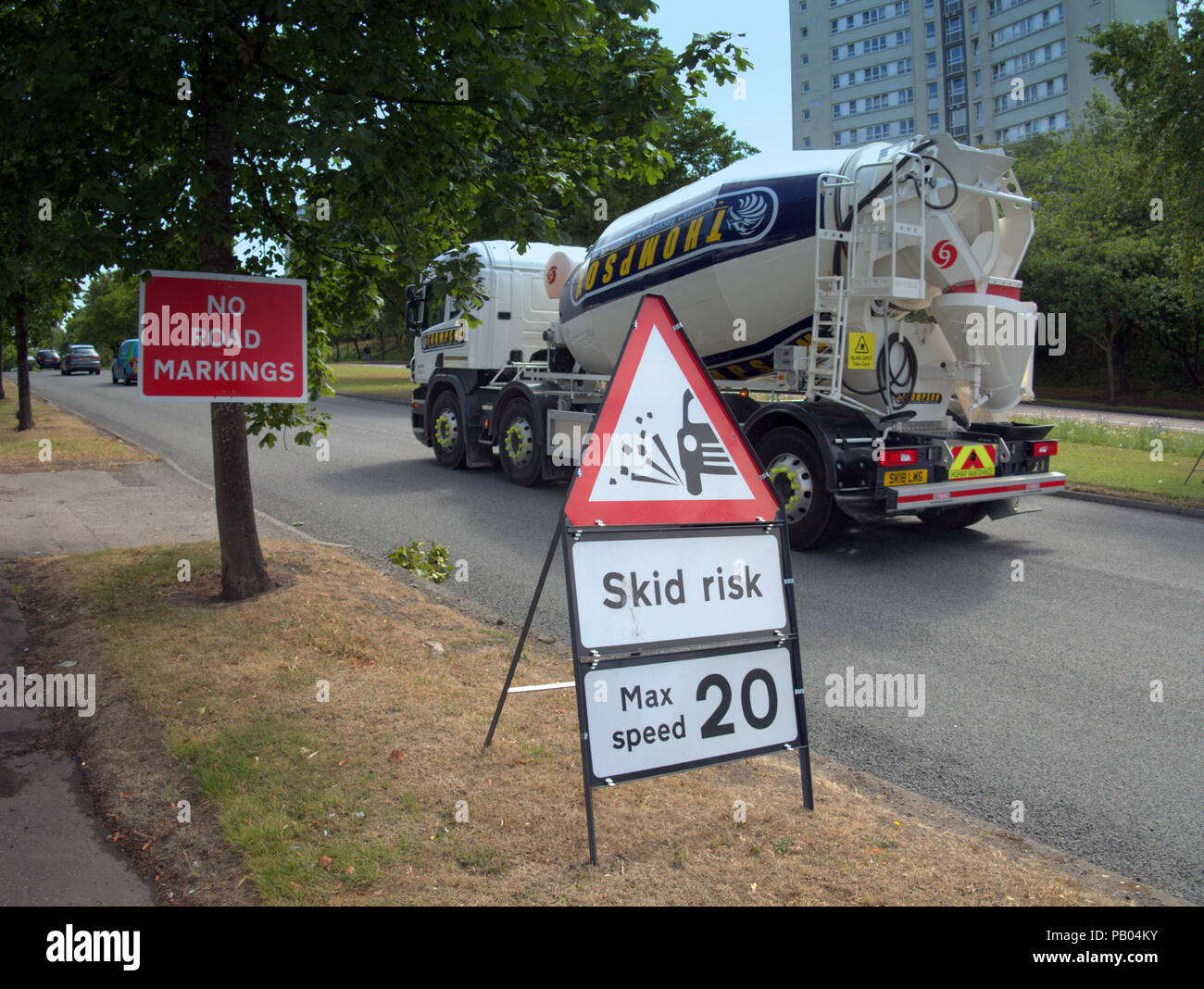 cement mixer truck passing road signs skid risk max speed 20 and no road markings - Stock Image