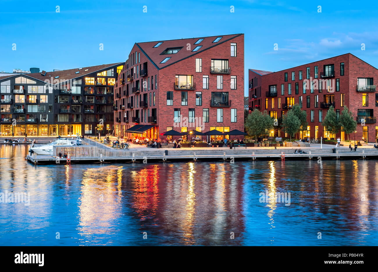 Kroyers Plads buildings of modern architecture design by embankment illuminated at night, Copenhagen, Denmark - Stock Image