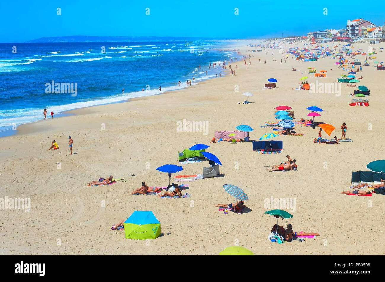 ESPINHO, PORTUGAL - JUL 30, 2017: People sunbathe at the ocean beach. Portugal famous tourist destination for it's ocean beaches. - Stock Image