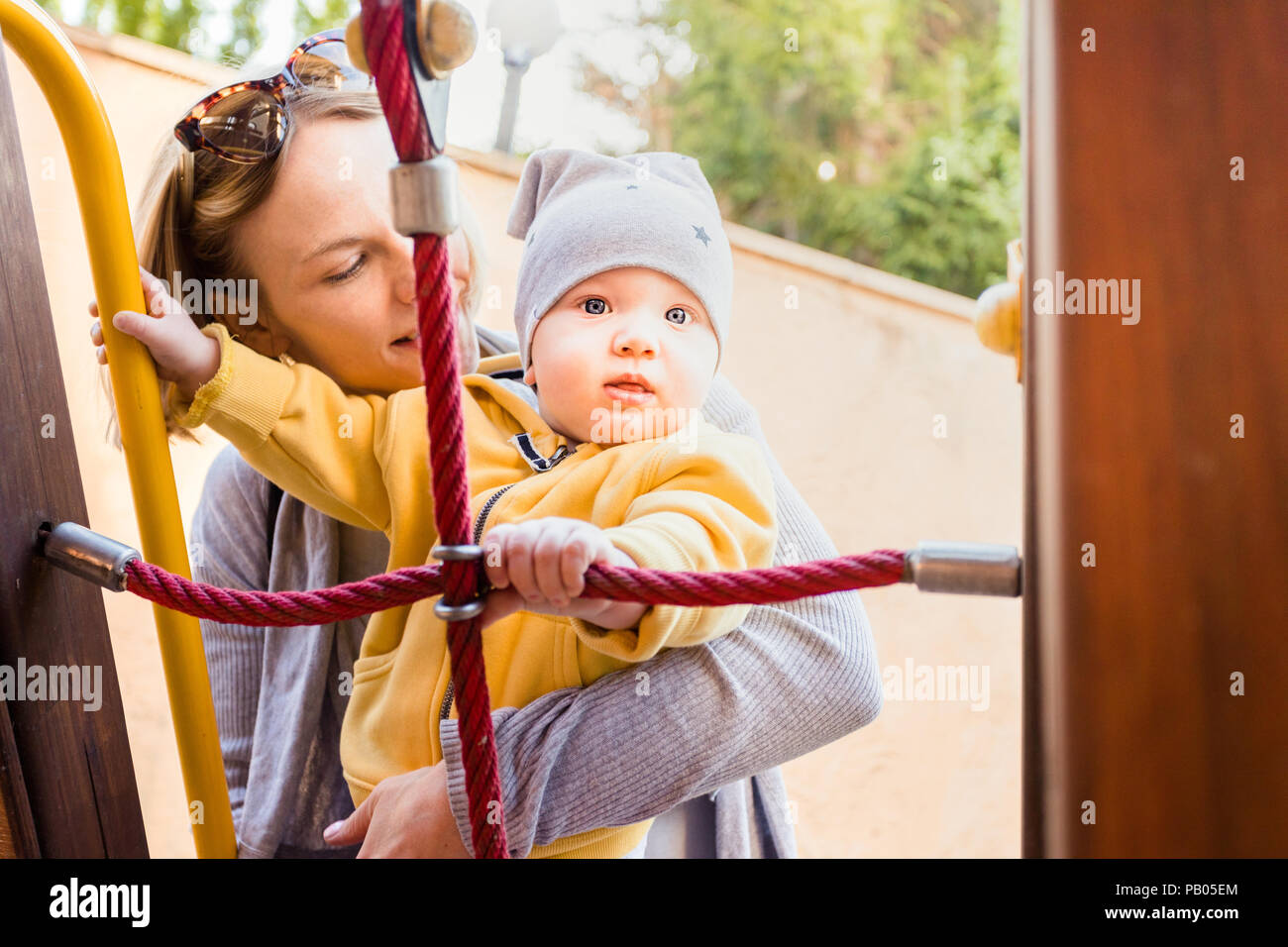 Mom and son climb the net of cables on the playground - Stock Image