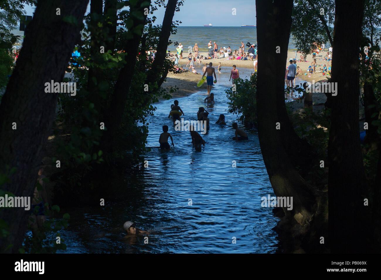 River mouth of Potok Oliwski (Oliwski Stream) in hot day on a crowded beach in Gdansk, Poland 20th July 2018 © Wojciech Strozyk / Alamy Stock Photo - Stock Image