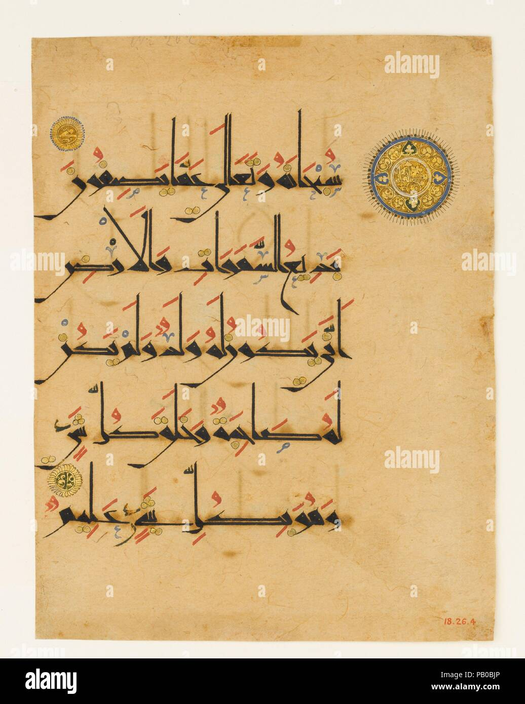 "Folio from a Qur'an Manuscript. Dimensions: H.10 in. (25.4 cm)  W. 7 1/4 in. (18.4 cm). Date: late 11th-12th century.  This folio from a Qur'an is written on paper in black new style script, with vocalizations in red, diacritical marks in gold, and other orthographical signs in blue and black. The golden medallions are verse markers: the smaller ones contain letter numerals, while the larger one contains the words ""100 verses"" encircled by a band of trefoil scrolls, indicating the beginning of the 100th verse of Sura 6 (al-An'am, ""of the Cattle"").  Paper, a Chinese invention, was first produce Stock Photo"