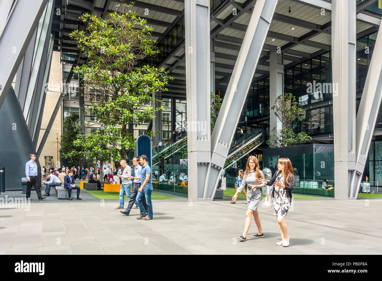 Men and women using and walking past the public space atrium at the foot of the Leadenhall Building in central London, England, UK - Stock Image