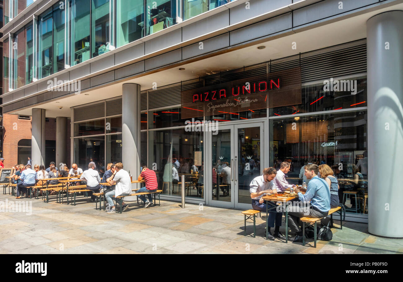 Customers sitting both outside and inside the Pizza Union Pizza restaurant on a hot summer day in Spitalfield, London, England, UK - Stock Image