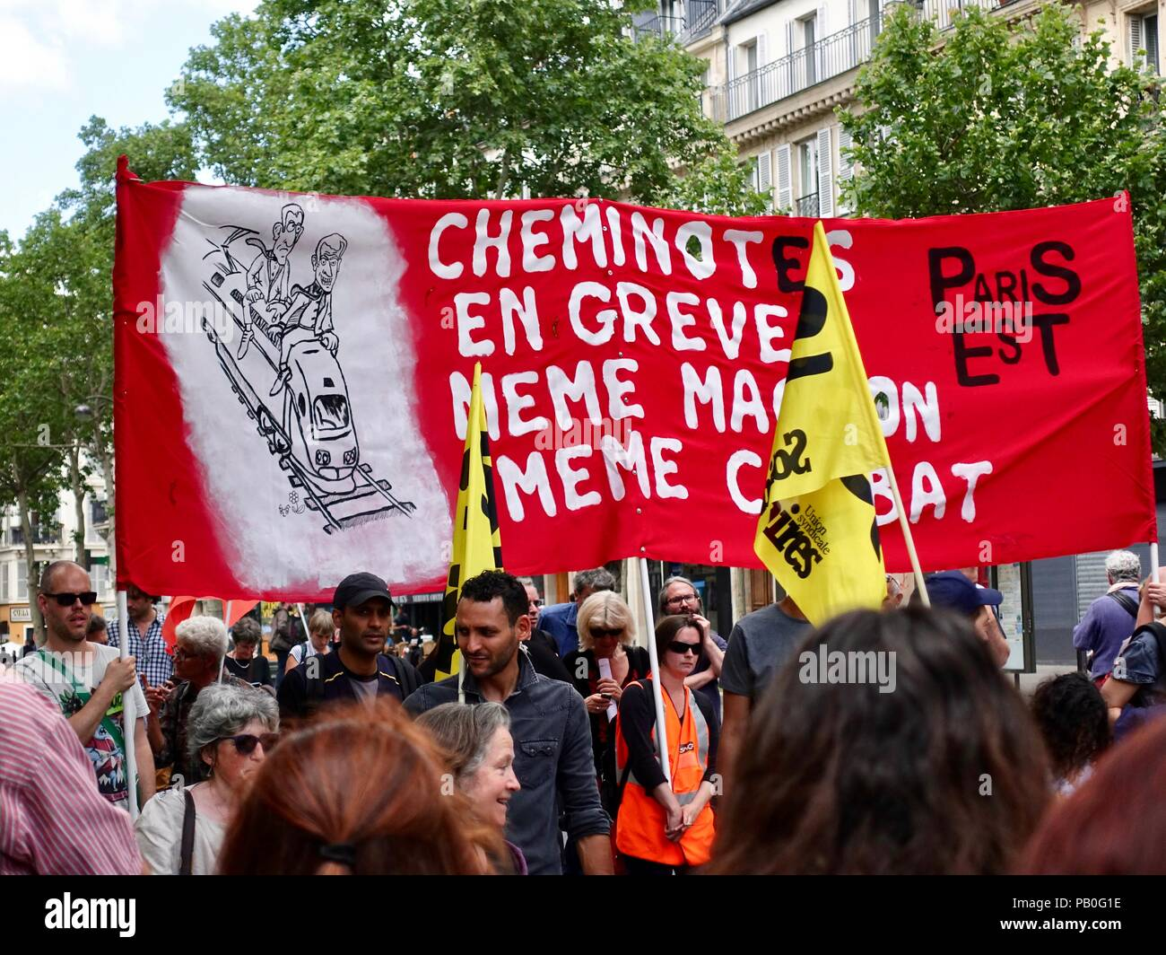 Striking train workers called 'cheminotes' carry a large red banner during a June demonstration against President Macron, Paris, France - Stock Image