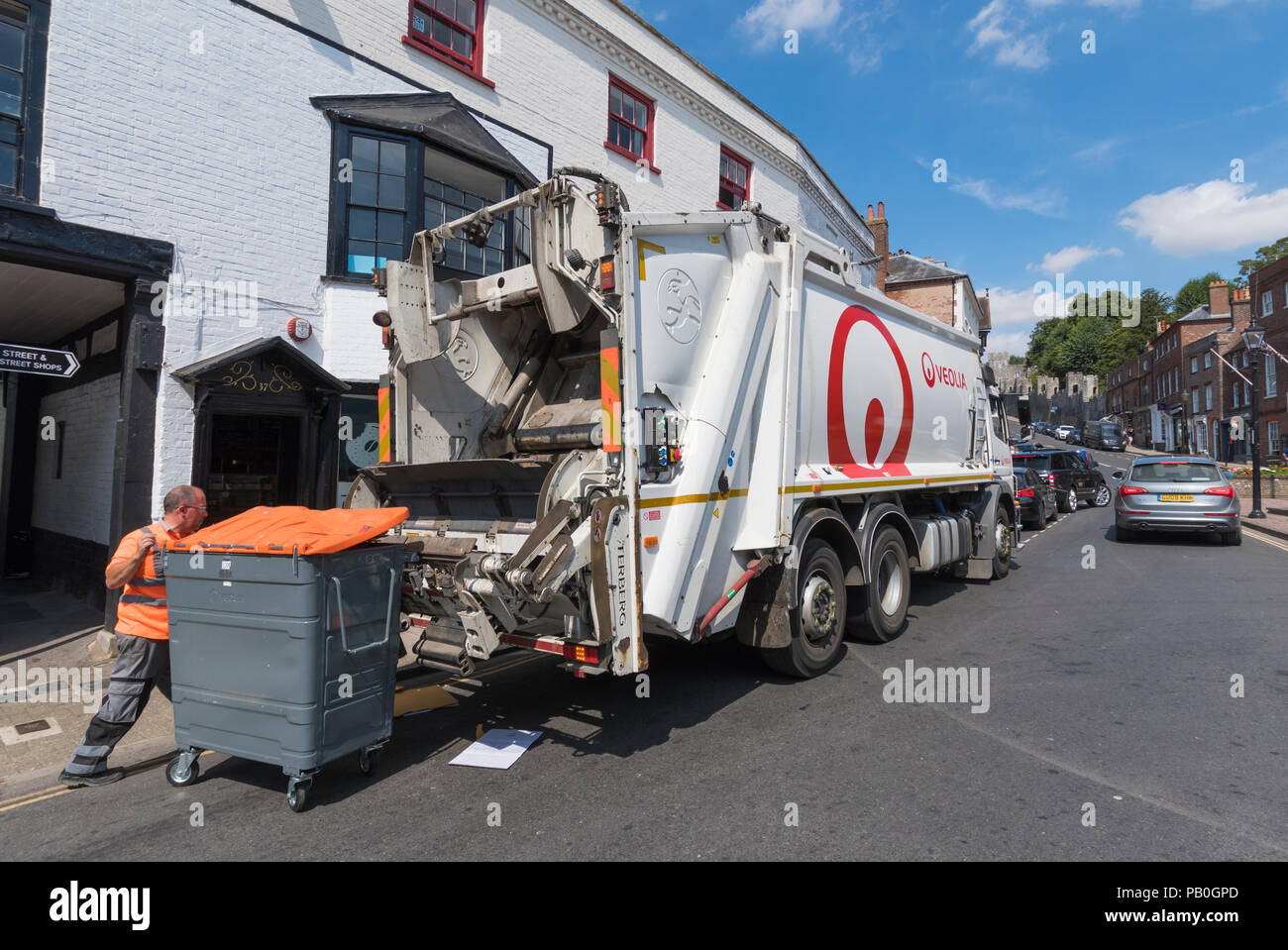 Veolia truck outside shops in a High Street collecting waste rubbish in Arundel, West Sussex, England, UK. - Stock Image