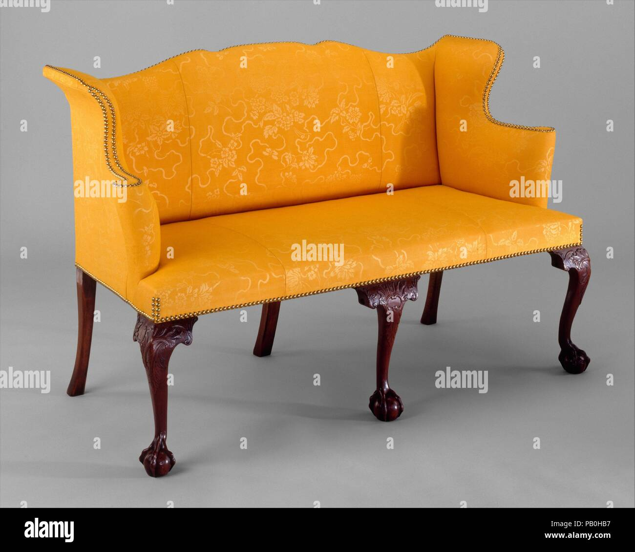 Settee. Culture: American. Dimensions: 36 3/8 x 57 1/2 x 26 in. (92.4 x 146.1 x 66 cm). Date: 1760-90.  This is one of only two fully upholstered cabriole-leg Massachusetts settees that are known today. It belongs to a small group of Boston furniture characterized by asymmetrically arranged C-scrolls and knee carving in foliage patterns. The flared wings and bow-shaped back are supreme manifestations of New England Rococo design. Museum: Metropolitan Museum of Art, New York, USA. - Stock Image