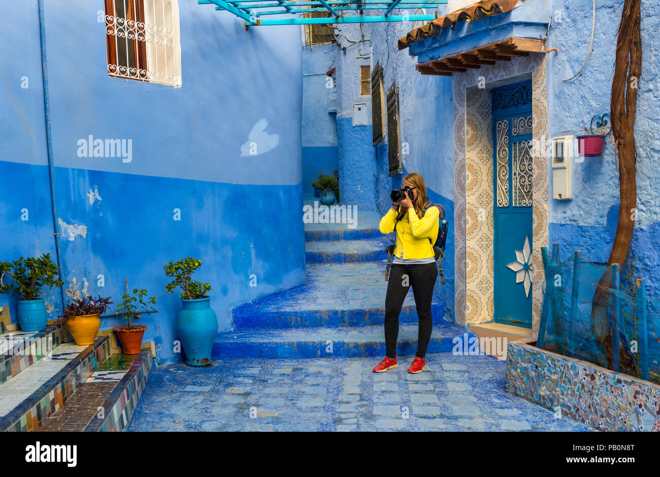 Young woman photographed, Blue house walls, Medina of Chefchaouen, Chaouen, Tangier-Tétouan, Kingdom of Morocco - Stock Image