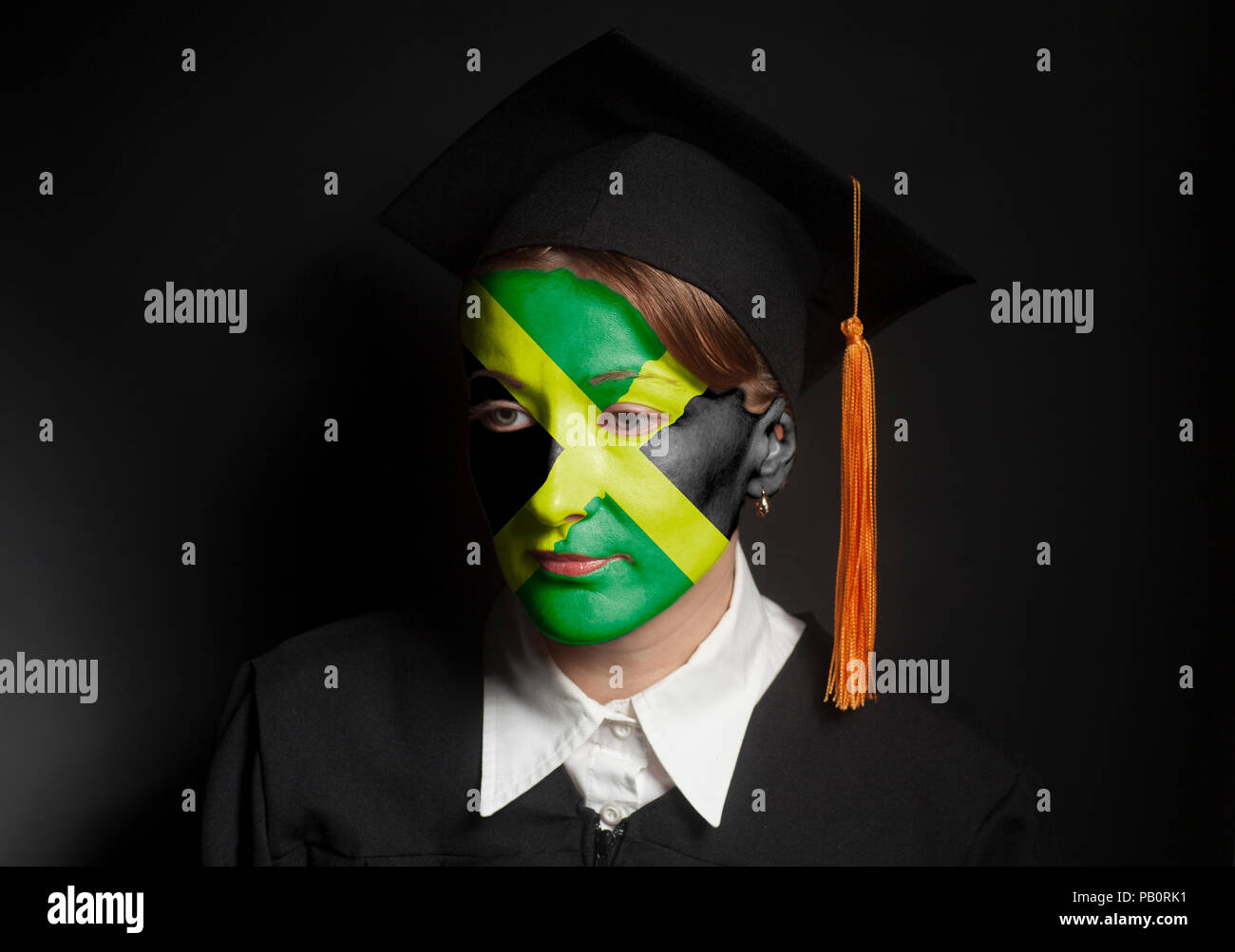Portrait of Female Jamaica bachelor with painted Jamaica flag in Black mantle and Graduation Cap on black - Stock Image
