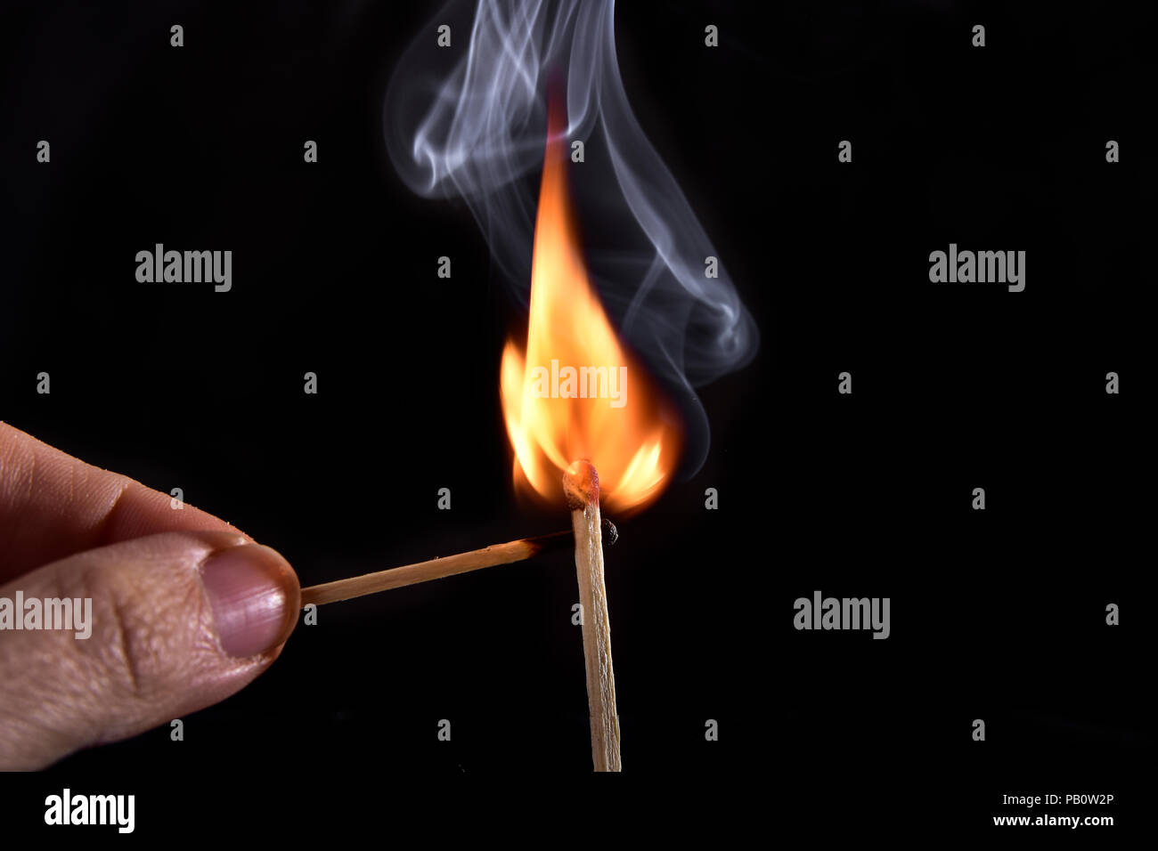 Close up of a match on a black background. I lit a matchstick on a dark background to see all the details of the sequence of ignition. - Stock Image