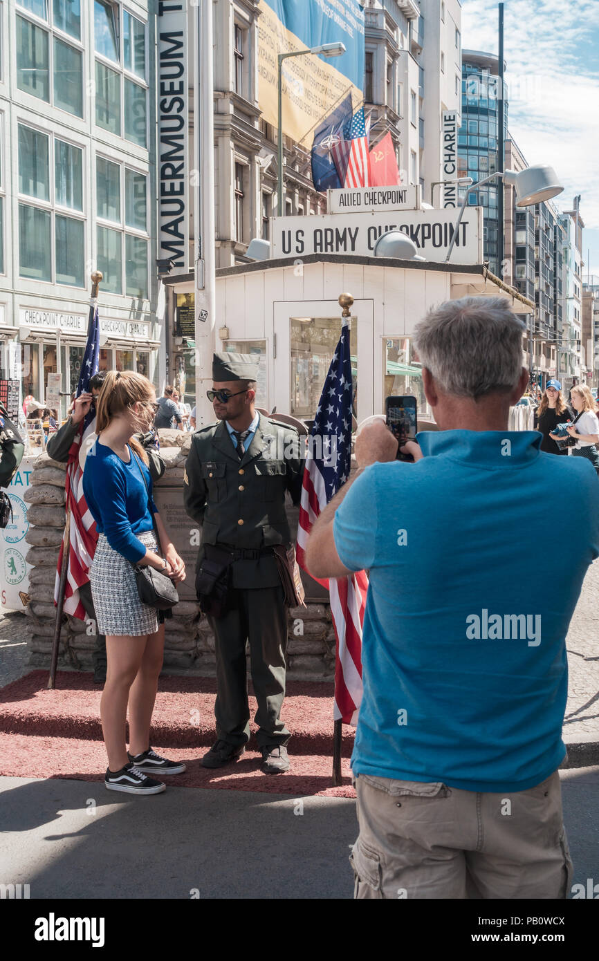People visiting Checkpoint Charlie, making photographs with American soldiers Stock Photo