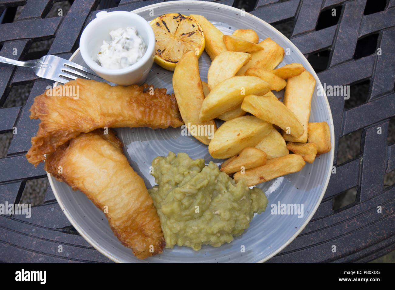Hotel Lunch fish of the day two battered lemon sole fillets with chunky chipped potatoes mushy peas and tartare sauce Stock Photo
