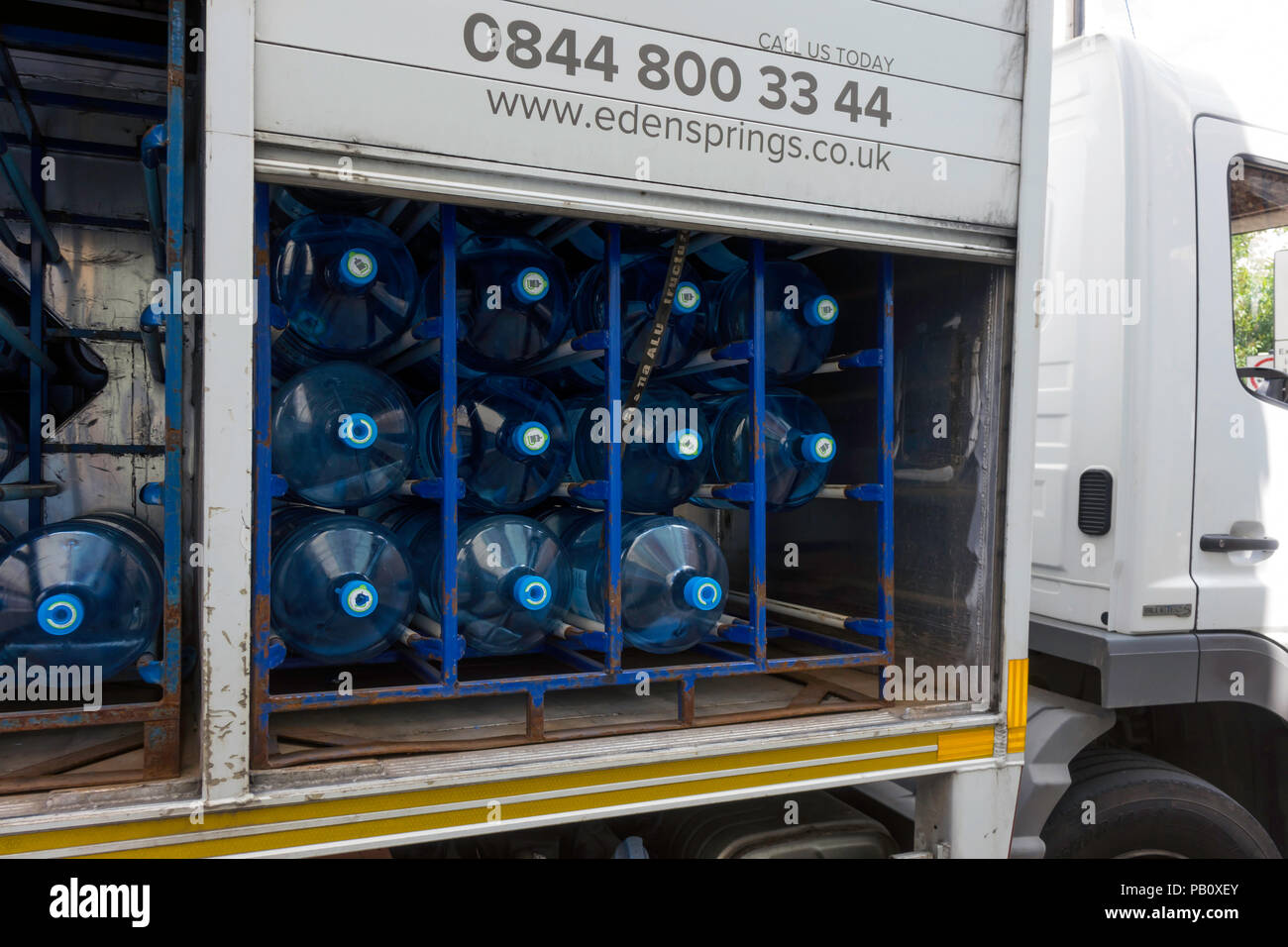 A lorry delivering large bottles of drinking water for use in commercial premises with side doors open Stock Photo