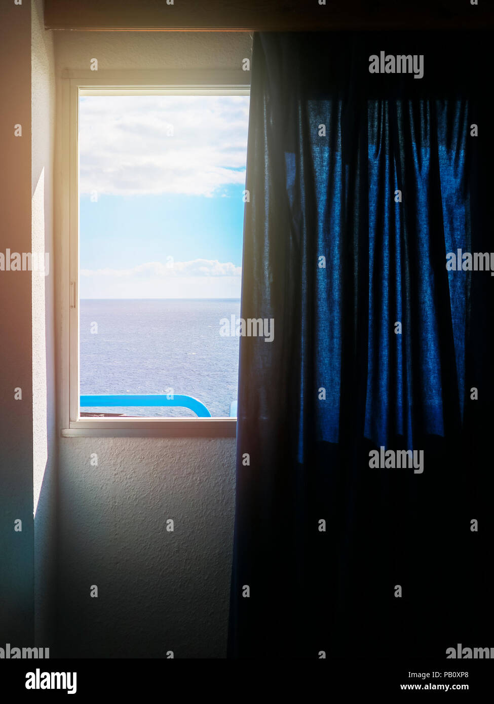 View from the window of hotel room, blue curtain, bright sunshine outside. - Stock Image
