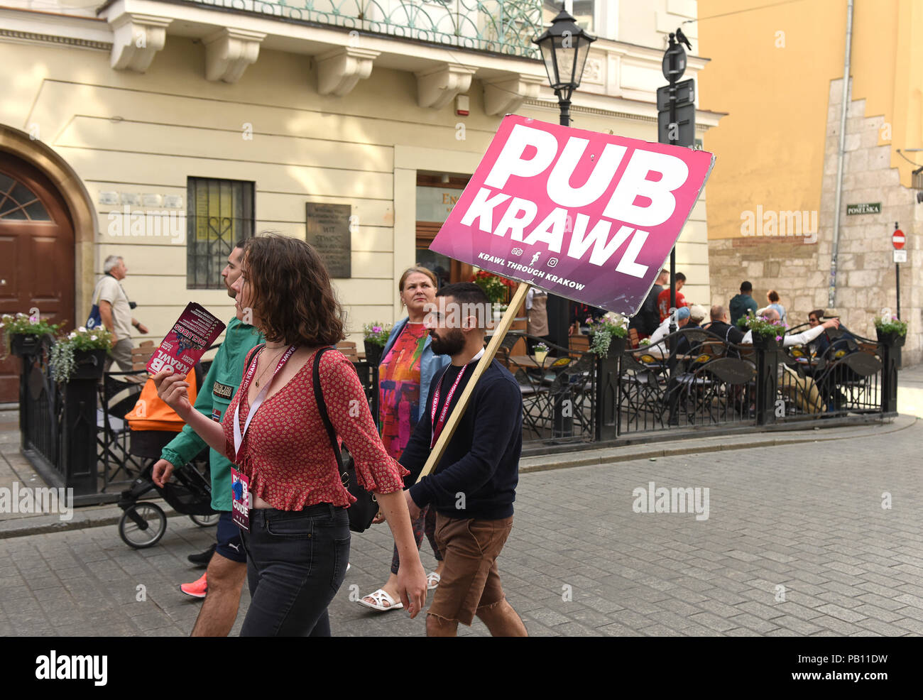 People advertising a pub crawl in Krakow Poland - Stock Image