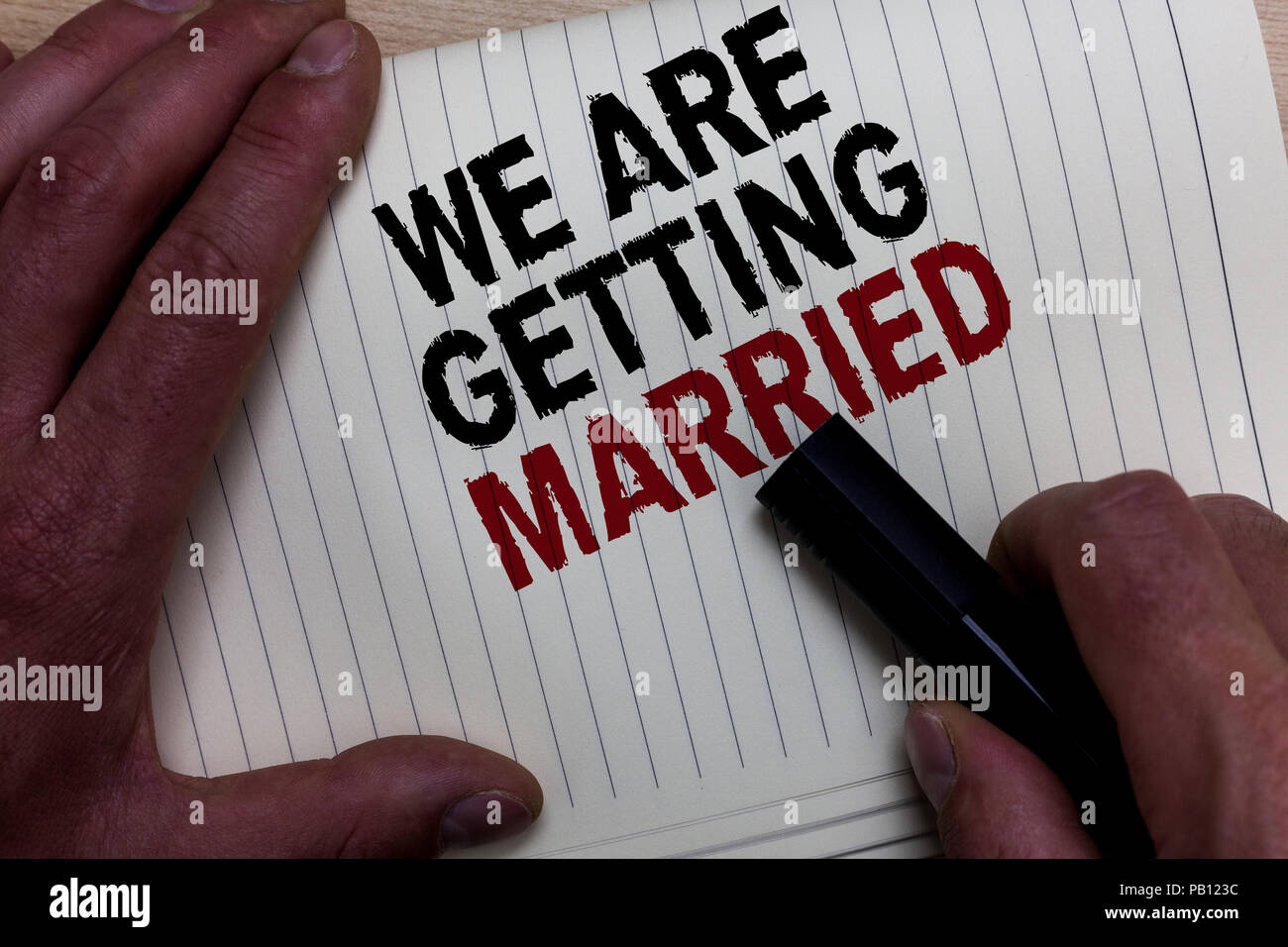 Word writing text We Are Getting Married. Business concept for Engagement Wedding preparation Loving couple Man's hand grasp black marker with some bl - Stock Image