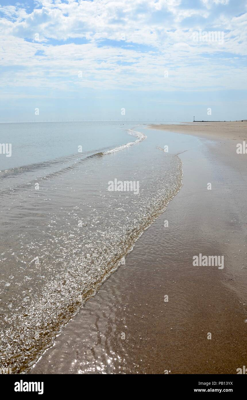 Tideline on Lincolnshire coast with wind turbines in distance, England, UK. - Stock Image