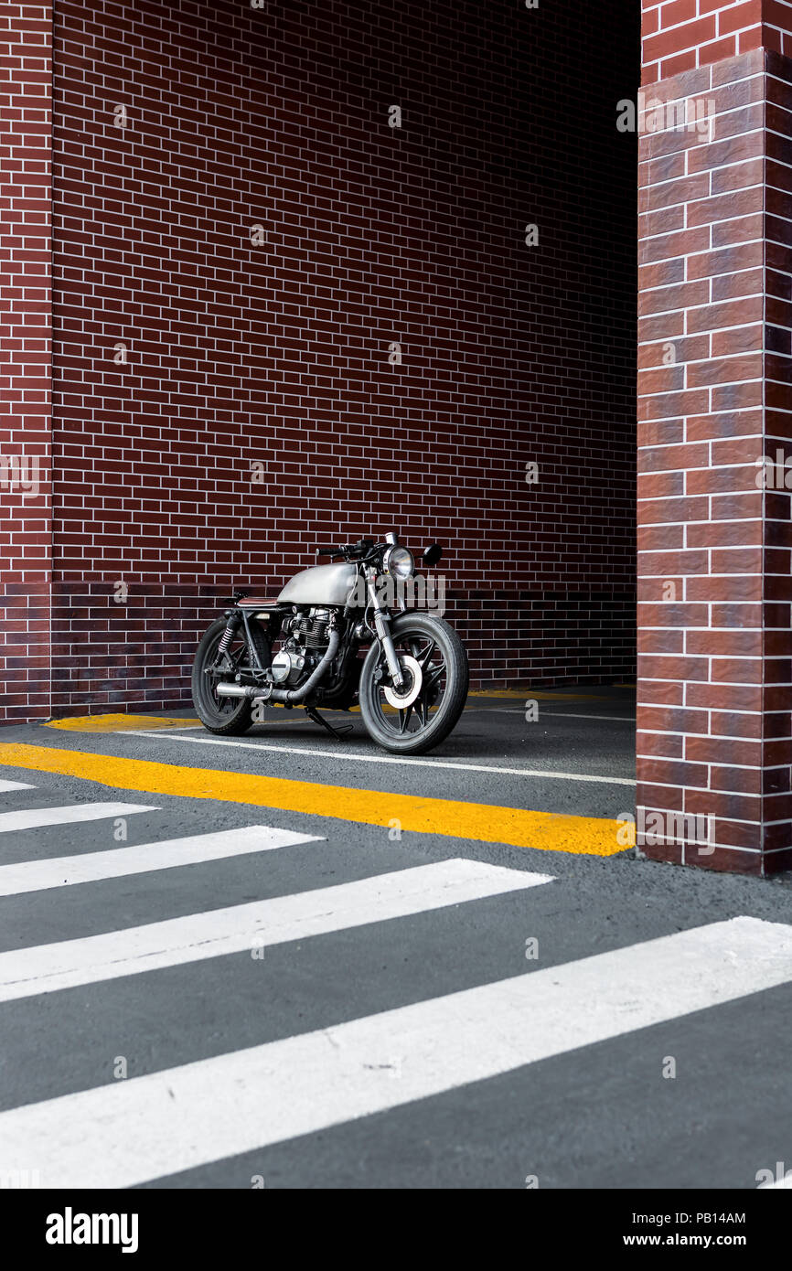 Caferacer motorbike parking near brick wall of finance building. Everything is ready for having fun driving the empty road on a motorcycle tour journe - Stock Image