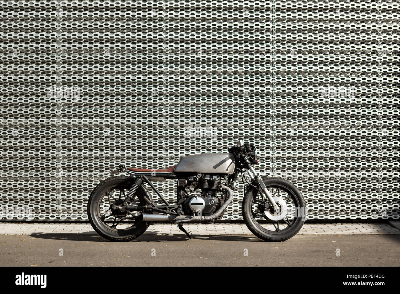 Custom motorcycle parking near wall of industrial building. Everything is ready for having fun driving the empty road on a motorcycle tour journey. Mo - Stock Image